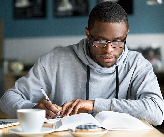 male_student_reading_book_and_writing