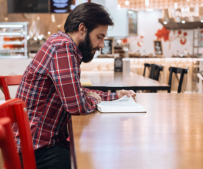 man_with_beard_reading_bible_in-cafe